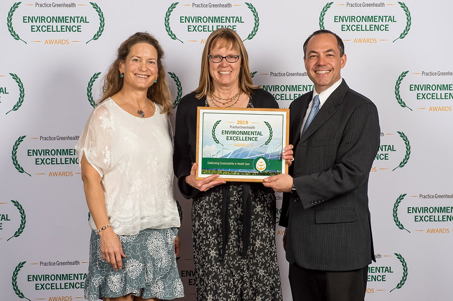 three people accepting environmental excellence award