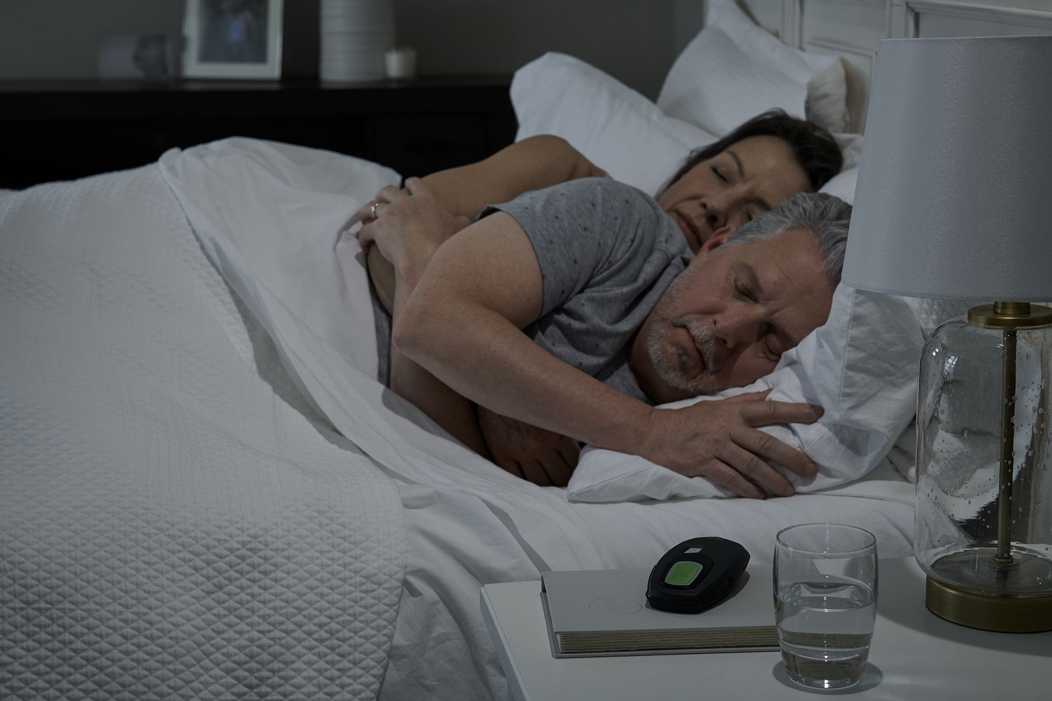 couple in bed sleeping near inspire remote